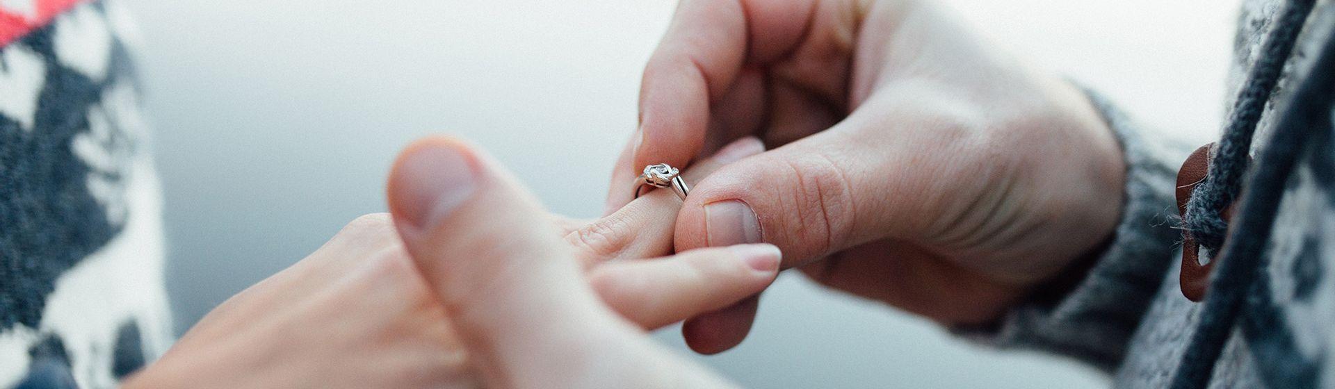 Een man die een ring om de ringvinger schuift bij zijn verloofde   Het Notarieel